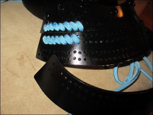 Die Schutzplatte für den Halsschutz der Samurai Rüstung werden nach historischem Vorbild verknüpft.