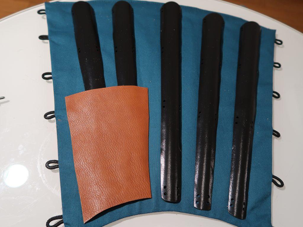 Der Lederbesatz folgt in seiner Form dem Sunate. Er deckt die unteren Enden der beiden Schutzplatte ab.
